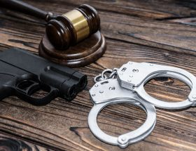 handcuffs, a judge hammer, a gun on a wooden background. criminal offense