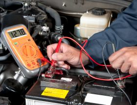 Auto mechanic checking car battery voltage